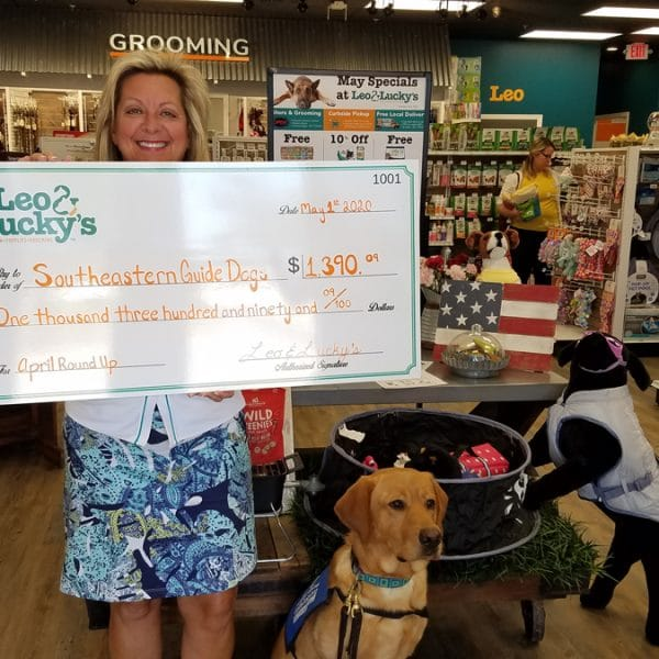 southeastern guide dogs rep with donation check from leo and luckys